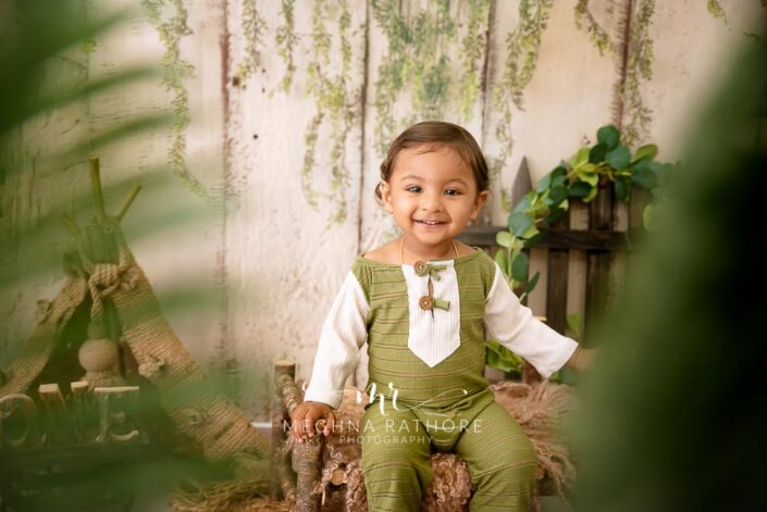 1 year old adorable boy posing in green and white colored outfit at meghna rathore photography in delhi gurgaon