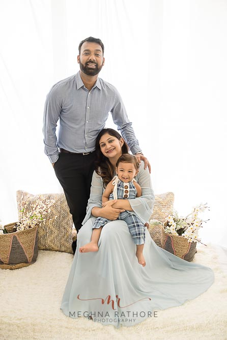 Family portrait with one year old baby boy all posing and smiling at meghna rathore photograhy in delhi gurgaon