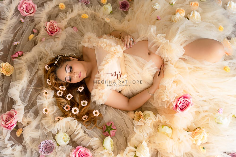 delhi maternity glamour photography mother wearing peach gown lying on ground flower decoration meghna rathore