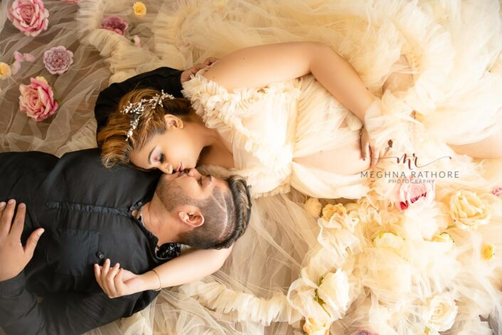 Maternity professional photoshoot husband and wife lying next to each other and posing at meghna rathore photography in delhi gurgaon