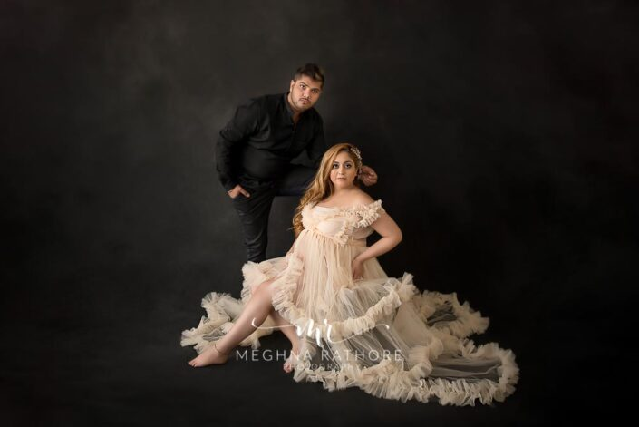 maternity couple professional photo shoot lady in gown husband in black dress delhi