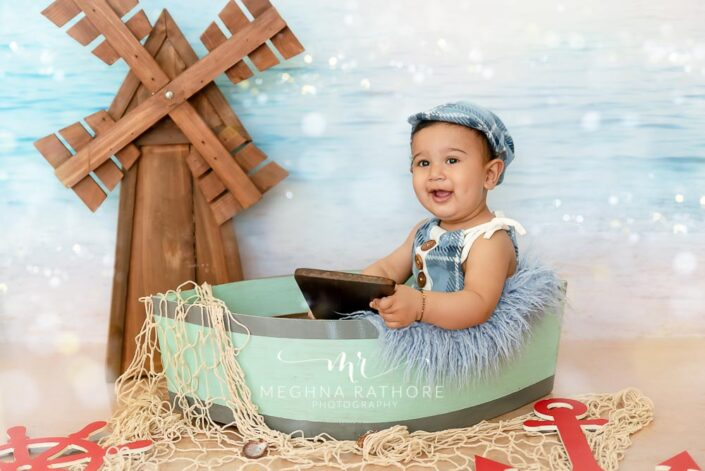 7 months old baby boy wearing adorable blue outfit sitting and posing with ship theme based professional photoshoot at meghna rathore photography in noida