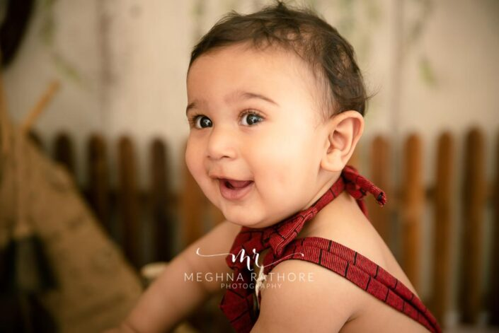 7 months old baby boy wearing adorable red outfit and smiling posing professional photoshoot at meghna rathore photography in noida