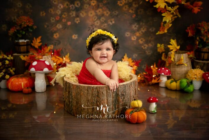 7 months old baby girl wearing adorable red frock sitting inside a wooden trunk and posing professional photoshoot at meghna rathore photography in noida
