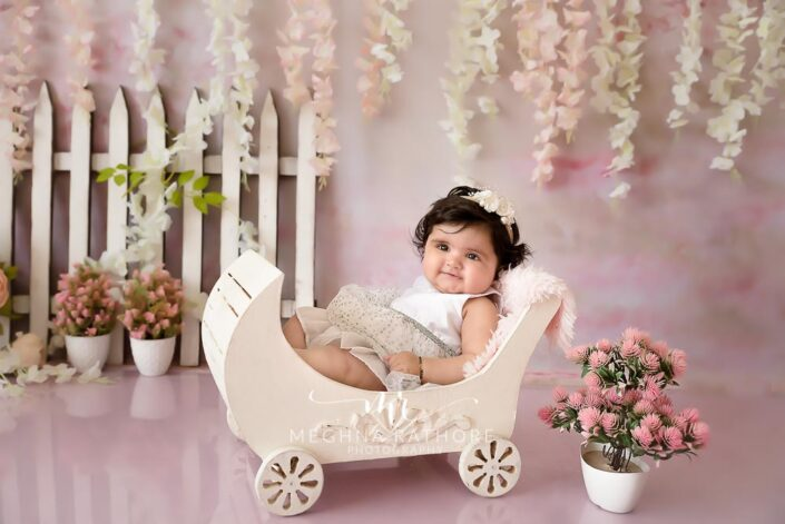 7 months old baby girl wearing adorable white frock sitting in a cart and posing professional photoshoot at meghna rathore photography in noida