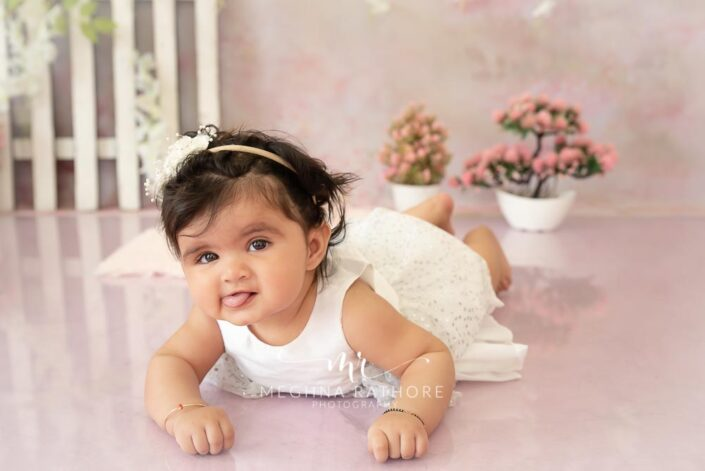 7 months old baby girl wearing adorable white frock and posing professional photoshoot at meghna rathore photography in noida