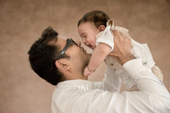 7 months old baby boy posing with father for professional photoshoot at meghna rathore photography in noida