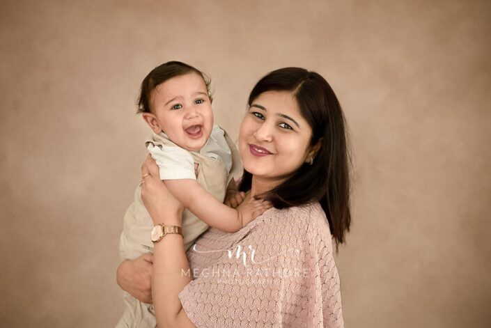 7 months old baby boy wearing white outfit and posing with his mother professional photoshoot at meghna rathore photography in noida
