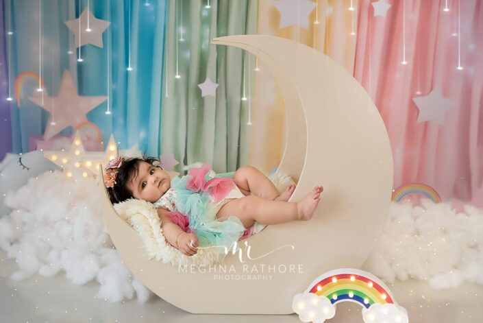 7 months old baby girl tucked in moon shaped and star props around her professional photoshoot at meghna rathore photography in delhi