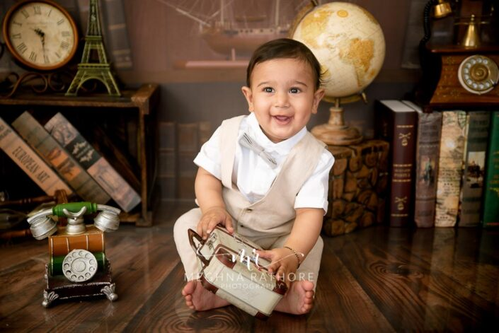 7 months old baby boy wearing white outfit sitting and posing with theme based professional photoshoot at meghna rathore photography in noida