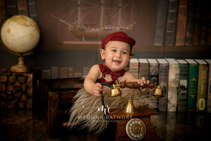 7 months old baby boy wearing adorable red outfit sitting and posing with theme based professional photoshoot at meghna rathore photography in noida