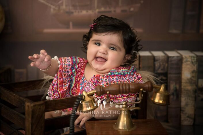 7 months old baby girl wearing adorable colorful outfit sitting and posing with theme based professional photoshoot at meghna rathore photography in noida