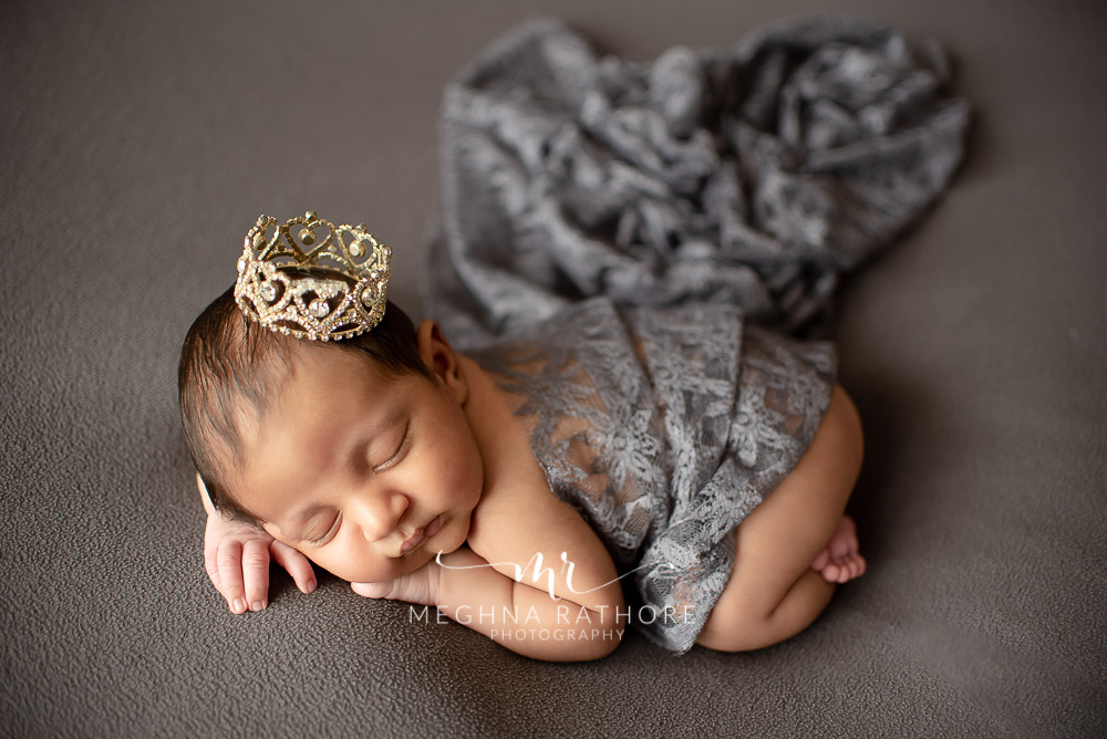 24 days old newborn baby boy posing adorably with props around in professional photoshoot set up at Meghna Rathore photography in gurgaun, new delhi and noida