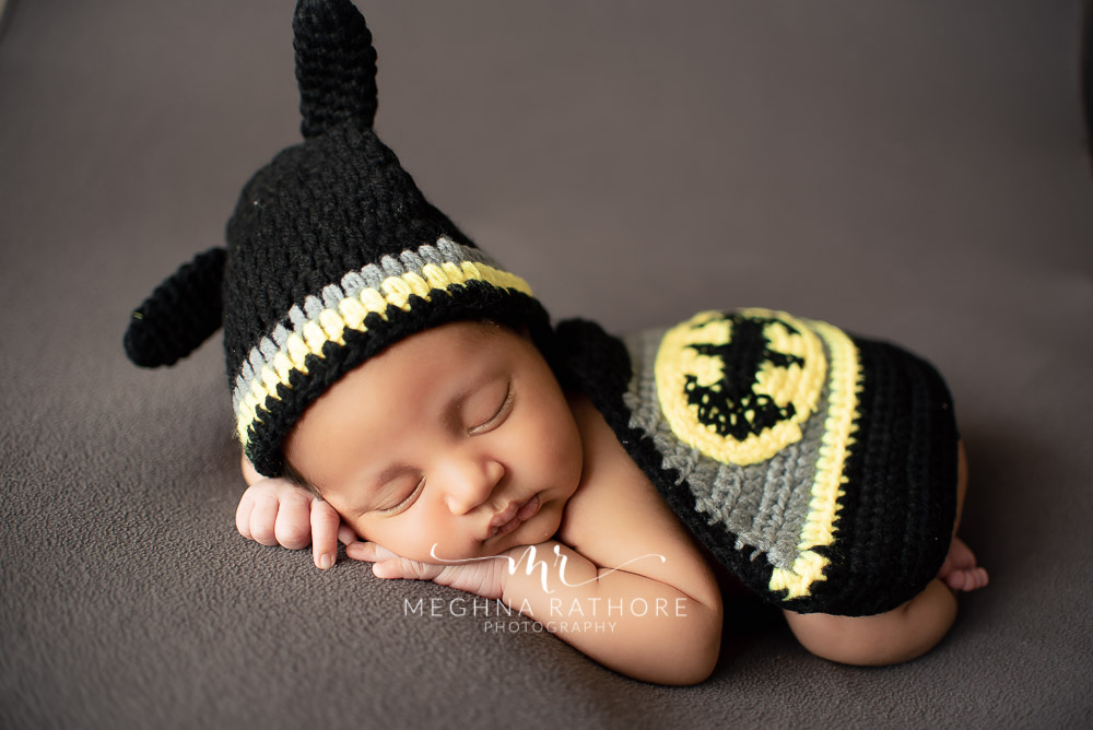 24 days old newborn baby boy posing in batman themed costume in professional photoshoot set up at Meghna Rathore photography in gurgaun, new delhi and noida