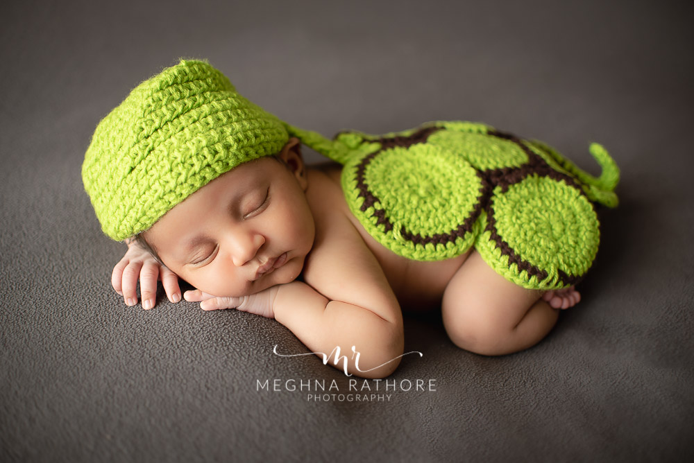 24 days old newborn baby boy posing adorably in cute outfit in professional photoshoot set up at Meghna Rathore photography in gurgaun, new delhi and noida