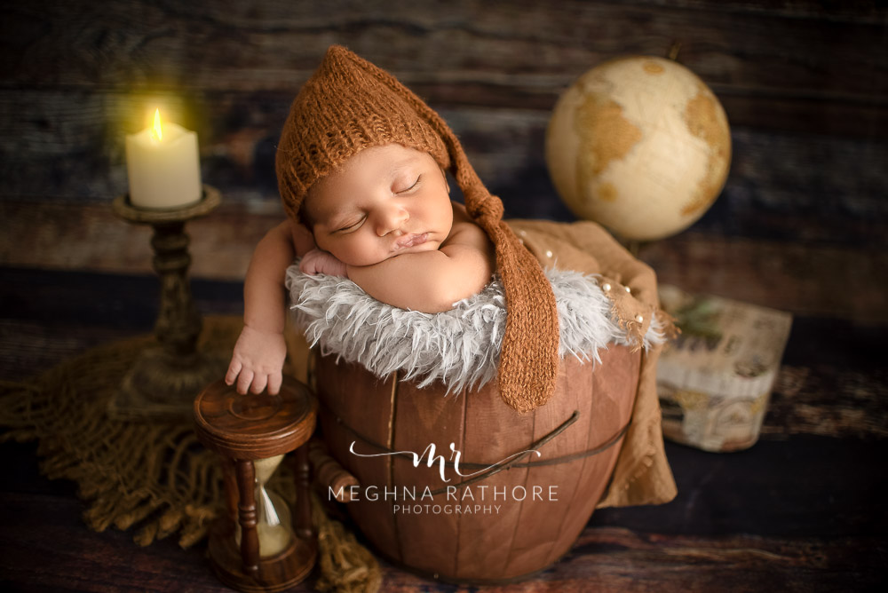 24 days old newborn baby boy posing adorably in cute outfit with a theme in professional photoshoot set up at Meghna Rathore photography in gurgaun, new delhi and noida