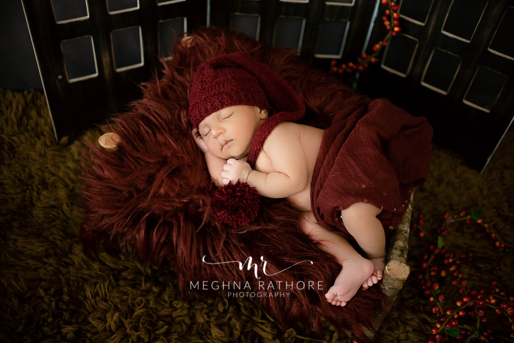 24 days old newborn baby boy posing adorably in cute outfit theme based in professional photoshoot set up at Meghna Rathore photography in gurgaun, new delhi and noida