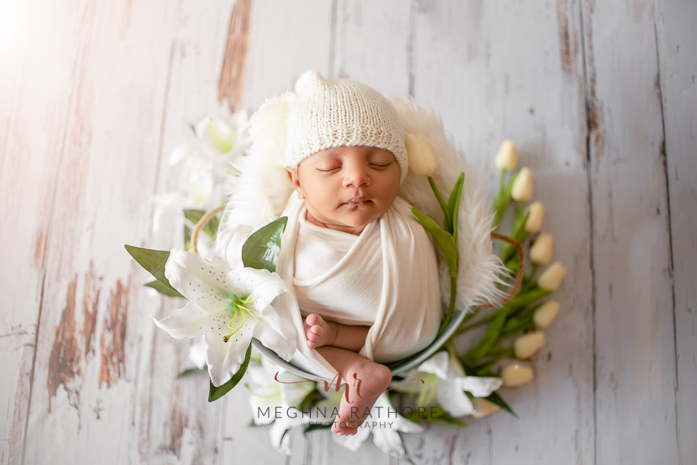 24 days old newborn baby boy posing adorably in cute white outfit top angle shot in professional photoshoot set up at Meghna Rathore photography in gurgaun, new delhi and noida