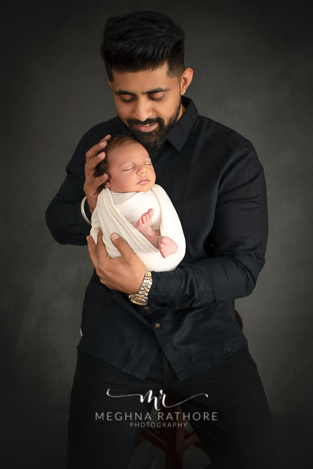 24 days old newborn baby boy posing with father in professional photoshoot set up at Meghna Rathore photography in gurgaun, new delhi and noida