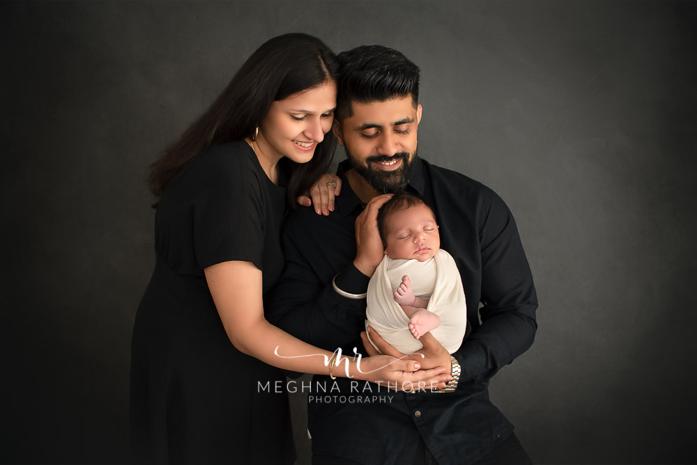 24 days old newborn baby boy posing with father and mother in professional photoshoot set up at Meghna Rathore photography in gurgaun, new delhi and noida