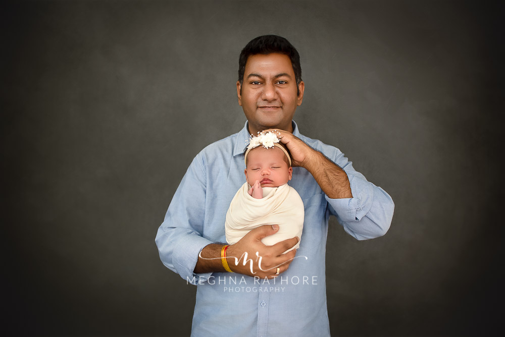 24 days old newborn girl child posing with father best indoor photo studio at meghna rathore photography in gurgaoun