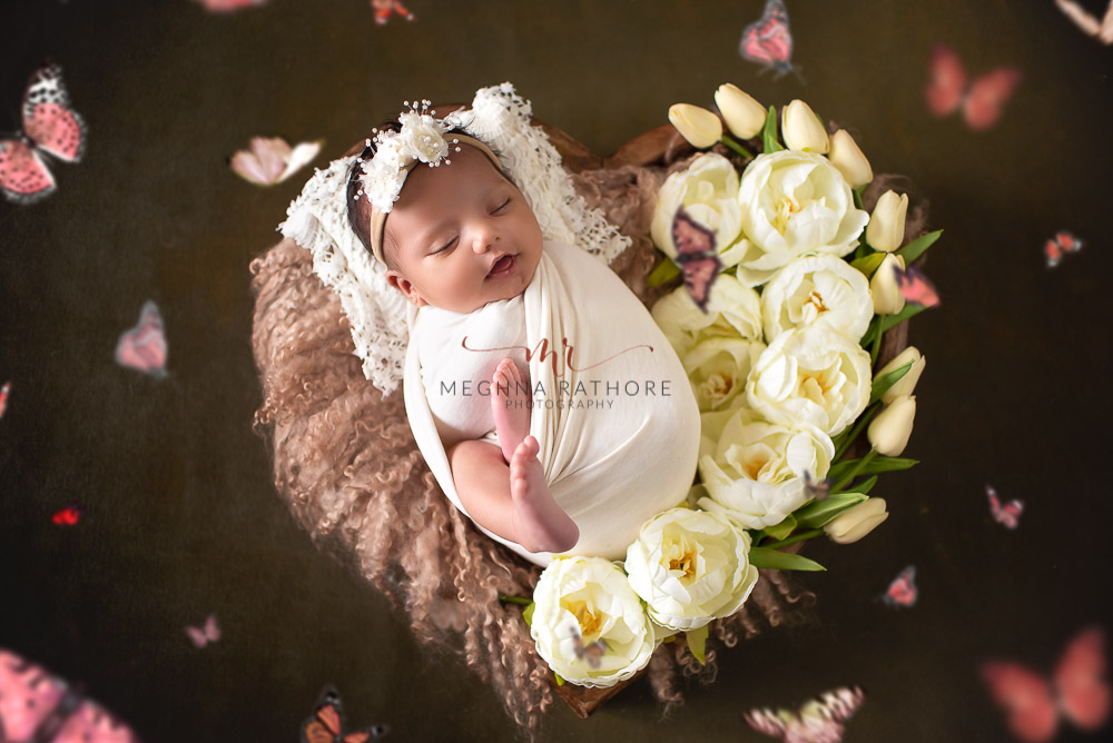 24 days old newborn girl child draped in white colored robe and butterflies around best indoor photo studio at meghna rathore photography in gurgaoun