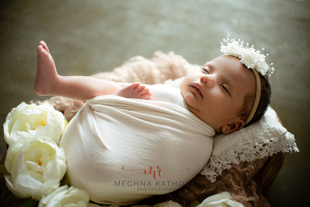 24 days old newborn girl child draped in white colored robe best indoor photo studio at meghna rathore photography in gurgaoun