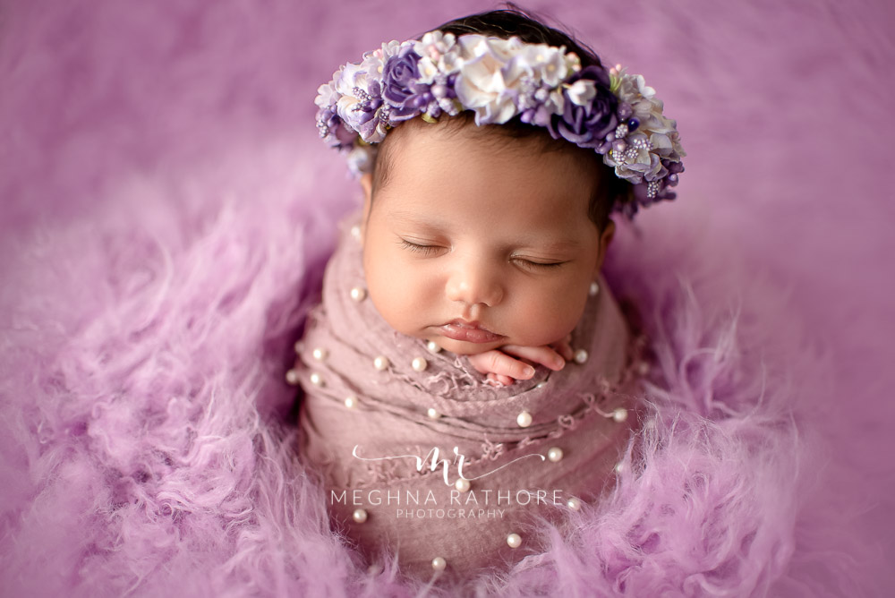 24 days old newborn girl child posing with a flower tiara over her head best indoor photo studio at meghna rathore photography in gurgaoun