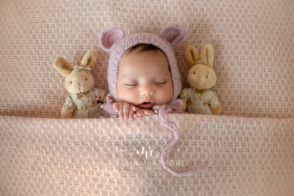 24 days old newborn girl child wearing a bunny shaped woolen cap with toys around her best indoor photo studio at meghna rathore photography in gurgaoun