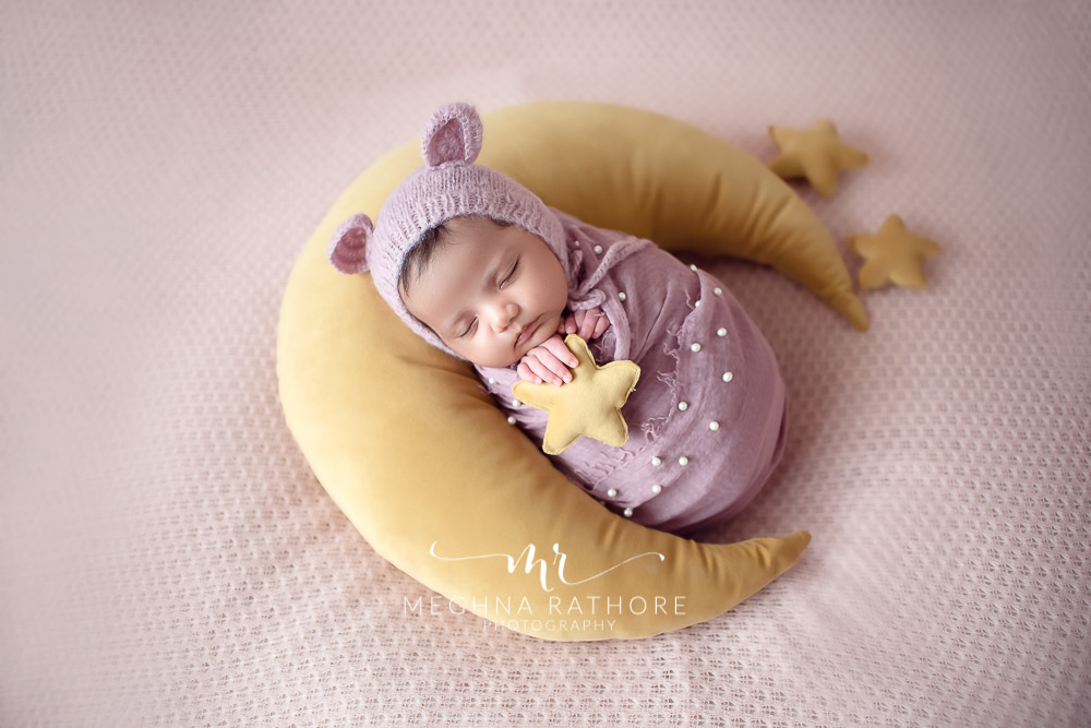 24 days old newborn girl child posing over a moon shaped pillow best indoor photo studio at meghna rathore photography in gurgaoun