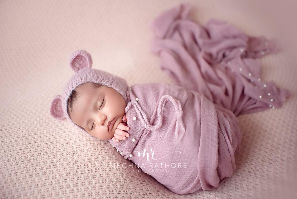 24 days old newborn girl child wearing a bunny shaped woolen cap best indoor photo studio at meghna rathore photography in gurgaoun