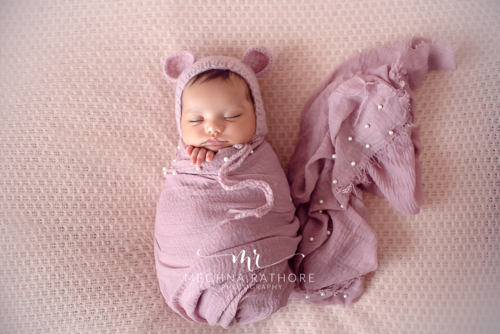 24 days old newborn girl child wearing a bunny shaped woolen cap and draped in purple colored cloth best indoor photo studio at meghna rathore photography in gurgaoun
