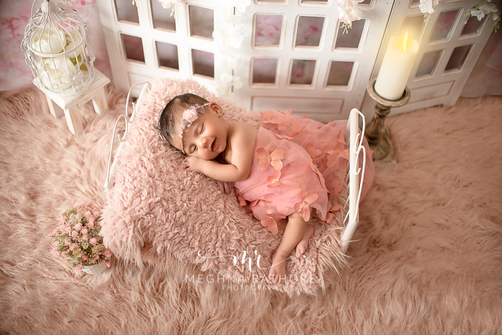 24 days old newborn girl child wearing a pink dress and smiling while lying on a bed in best indoor photo studio at meghna rathore photography in gurgaoun