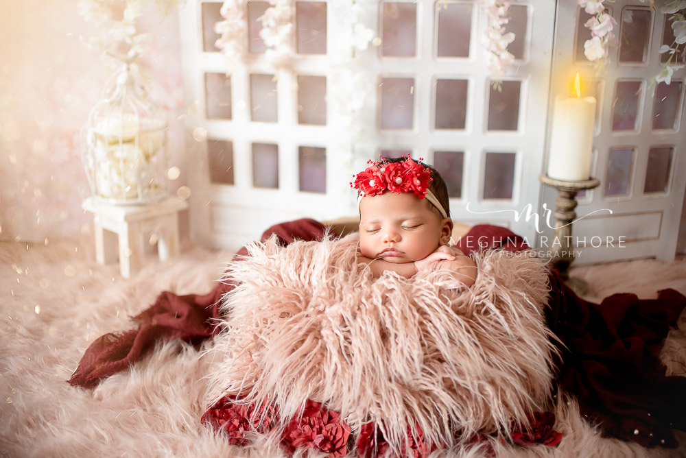 24 days old newborn girl child wearing a red flowered tiara and smiling while lying on a bed in best indoor photo studio at meghna rathore photography in gurgaoun