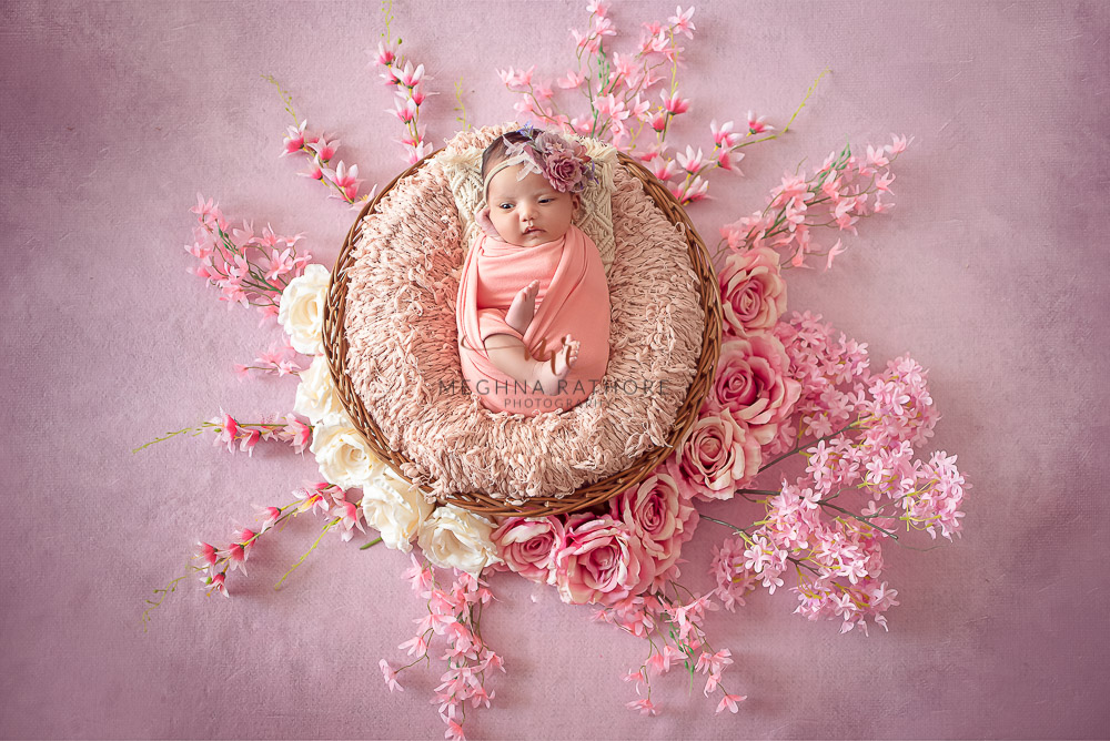 24 days old newborn girl child wearing a pink dress and smiling while lying on a basket in best indoor photo studio at meghna rathore photography in gurgaoun