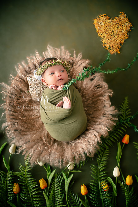24 days old newborn girl child best indoor photo studio baby posing and smiling draped in green colored robe at meghna rathore photography in gurgaoun