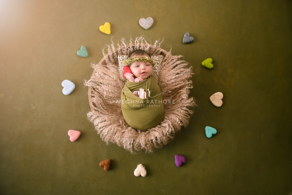 24 days old newborn girl child best indoor photo studio baby posing and smiling with heart shaped toys around her at meghna rathore photography in gurgaoun
