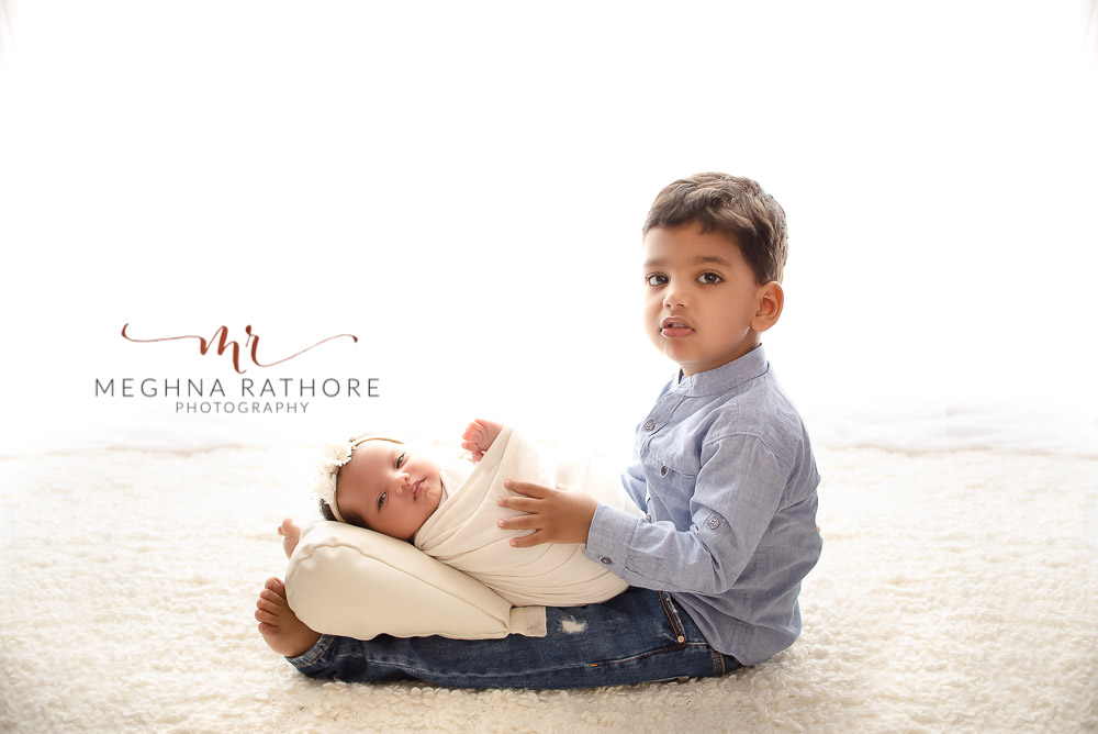 24 days old newborn girl child posing with big brother best indoor photo studio at meghna rathore photography in gurgaoun